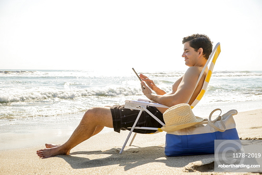 Side view of man sitting on deckchair and using digital tablet, Palm Beach, Florida