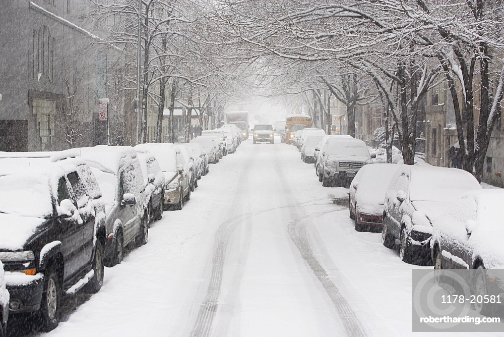 USA, New York City, snowy street with rows of parked cars