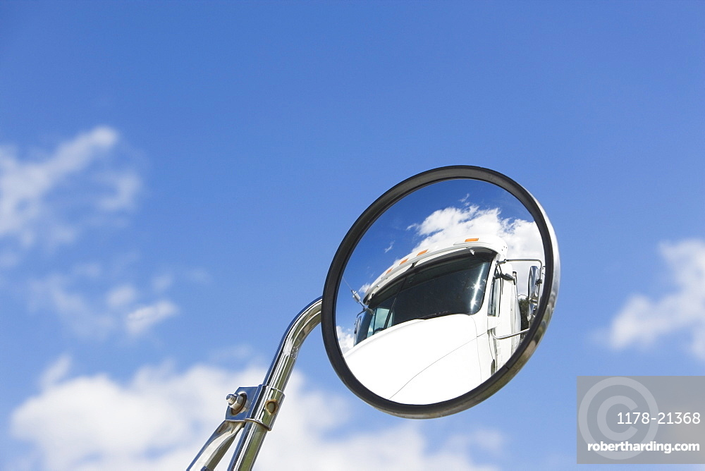 Reflection of semi-truck in side view mirror