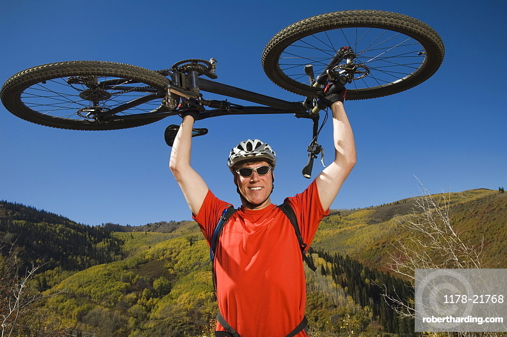 Man holding mountain bike over head, Utah, United States
