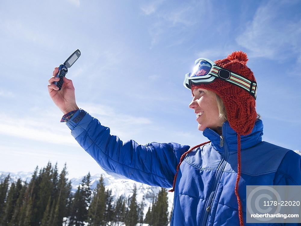 Woman in ski gear taking photograph