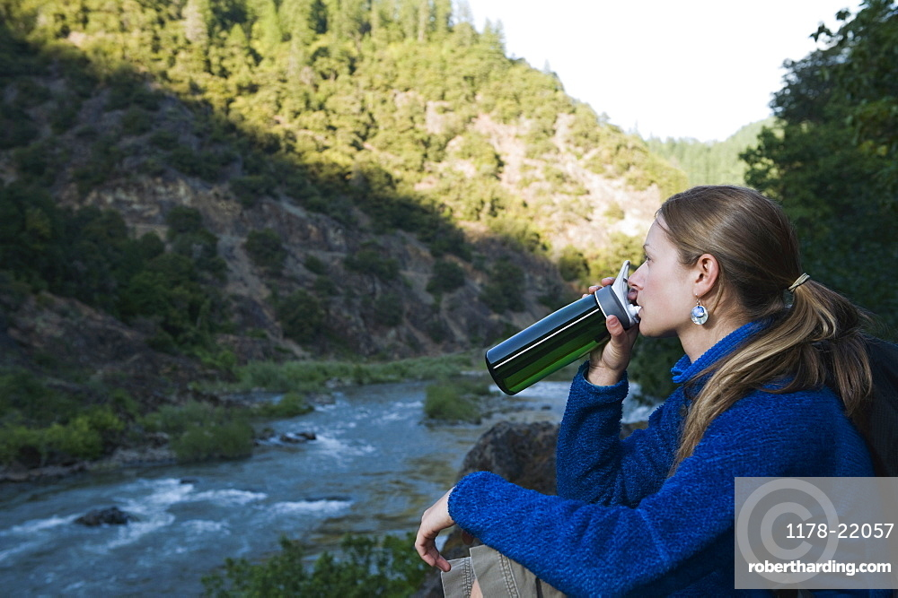 Young woman drinking water on river overlook
