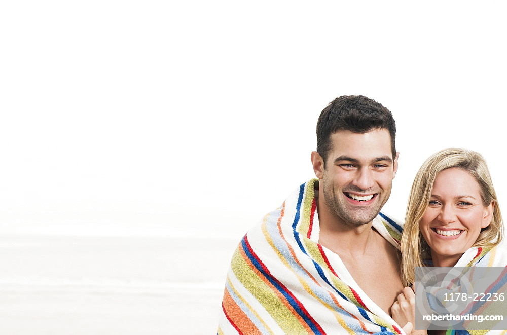 Portrait of couple wrapped in towel at beach