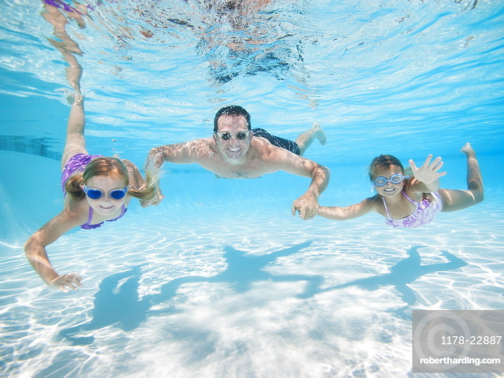 Father with two daughters (6-7,8-9) swimming underwater