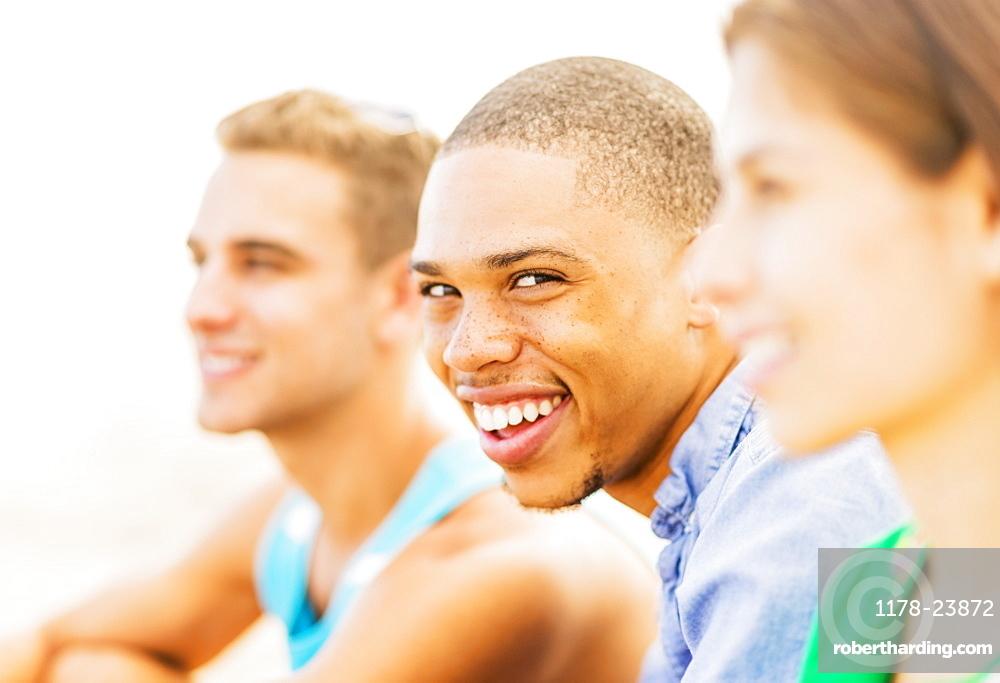 Portrait of young man smiling in between defocused friends