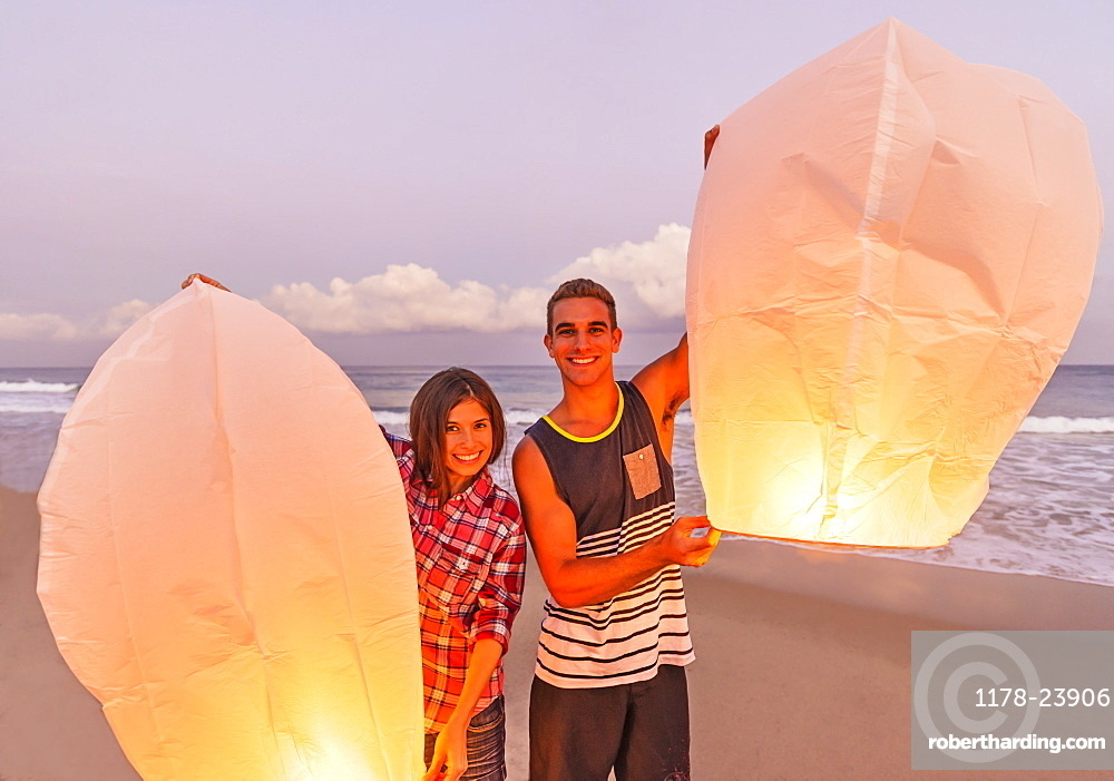 Young people with illuminated lanterns on beach