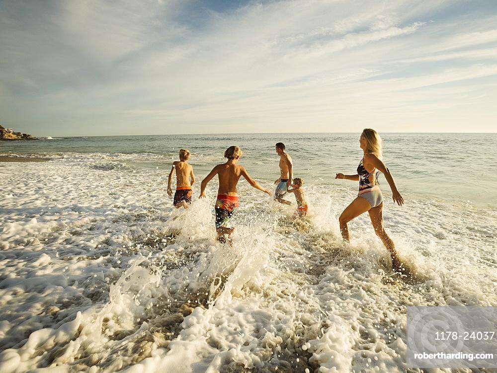 Family with three children (6-7, 10-11, 14-15) running on beach, Laguna Beach, California