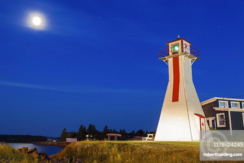 Lighthouse on grassy hill under full moon, Prince Edward Island, New Brunswick, Canada