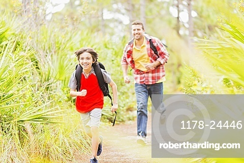 Father and son (12-13) running in forest, Jupiter, Florida