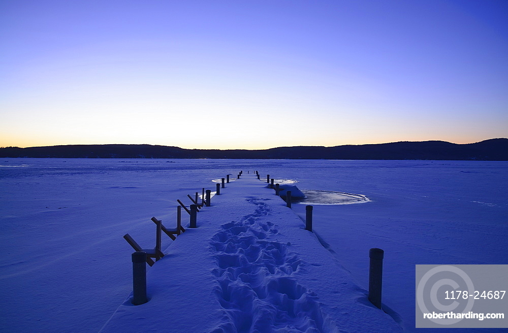 Symmetrical image of snowed jetty with footprints at dawn, hills on horizon, Lake George, New York