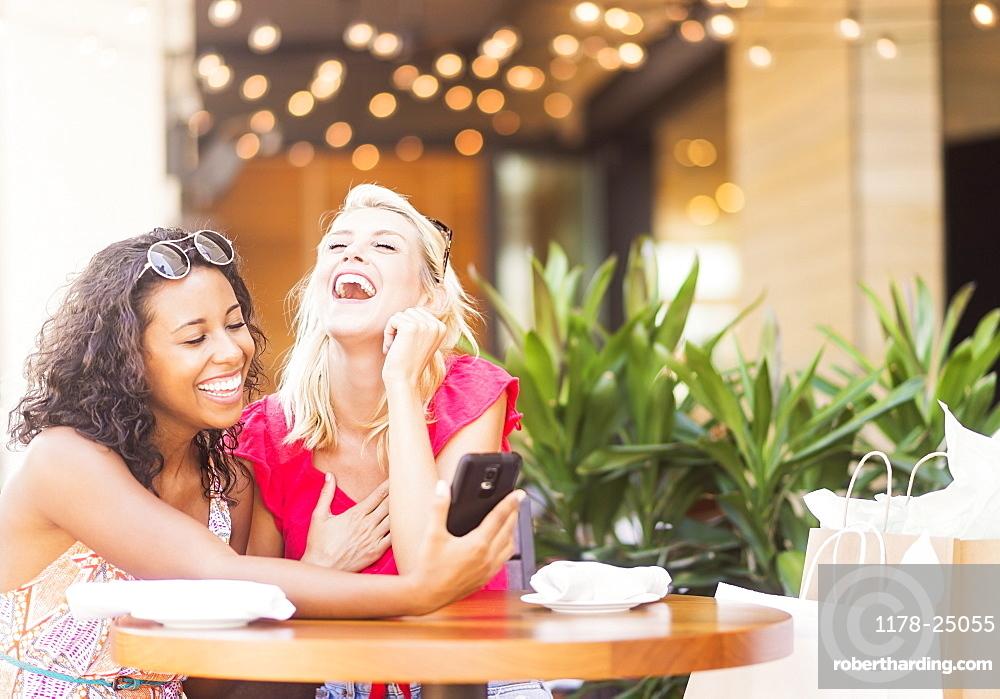 Female friends using smart phone in cafe