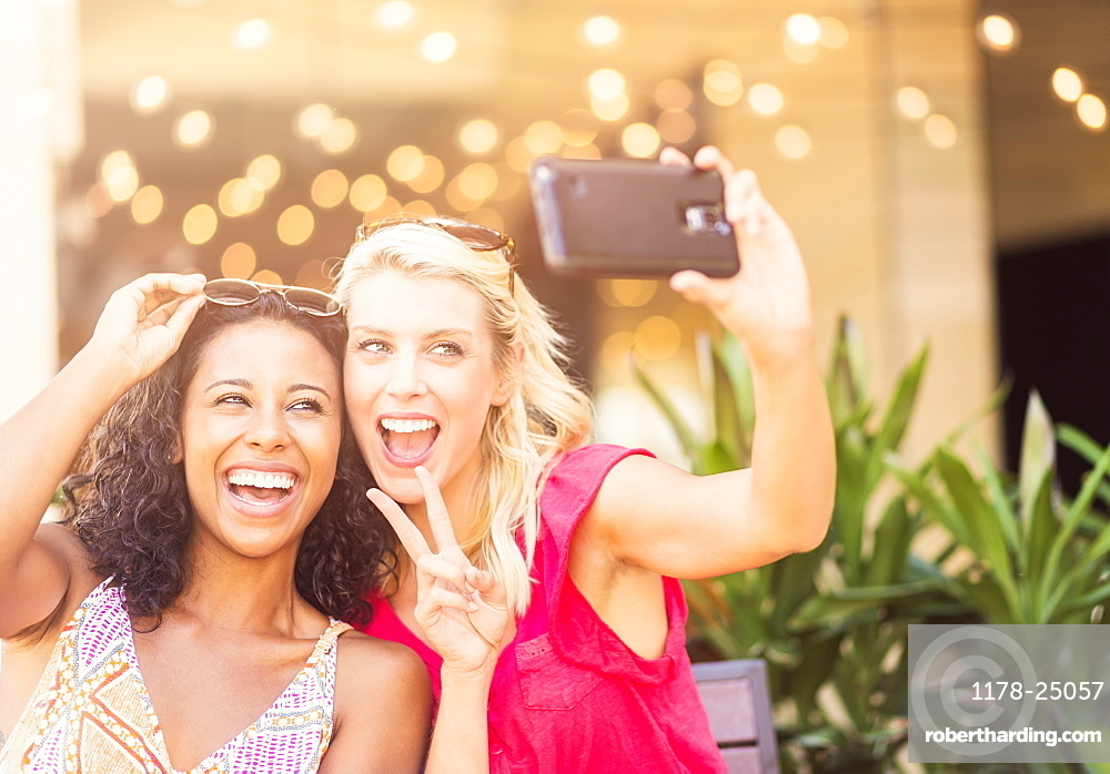 Female friends taking selfie with smart phone in cafe