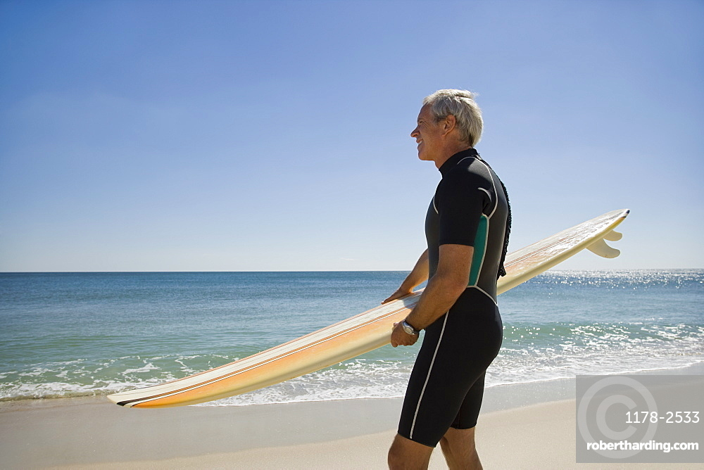 Man holding surfboard at beach