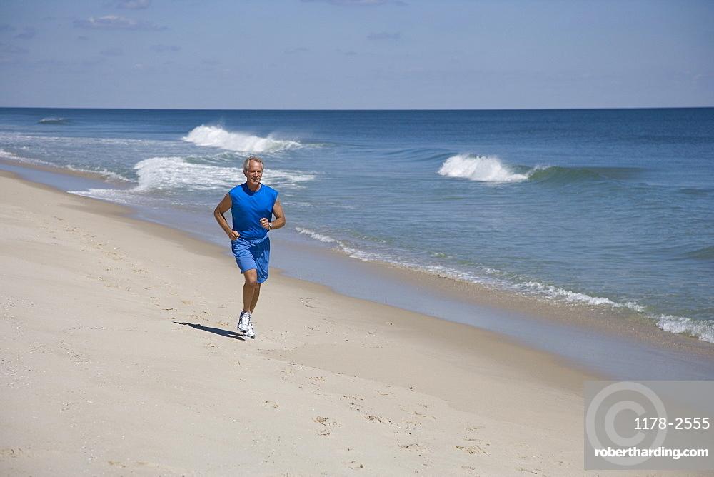 Senior man jogging on beach