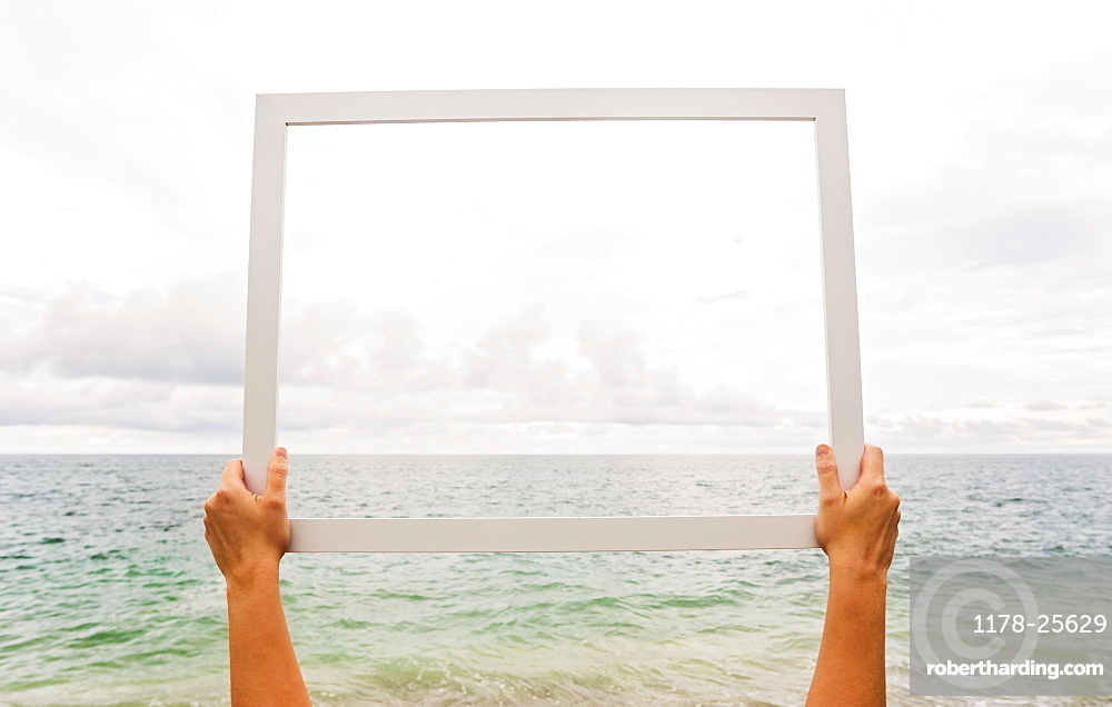 Person holding frame against cloudy sky