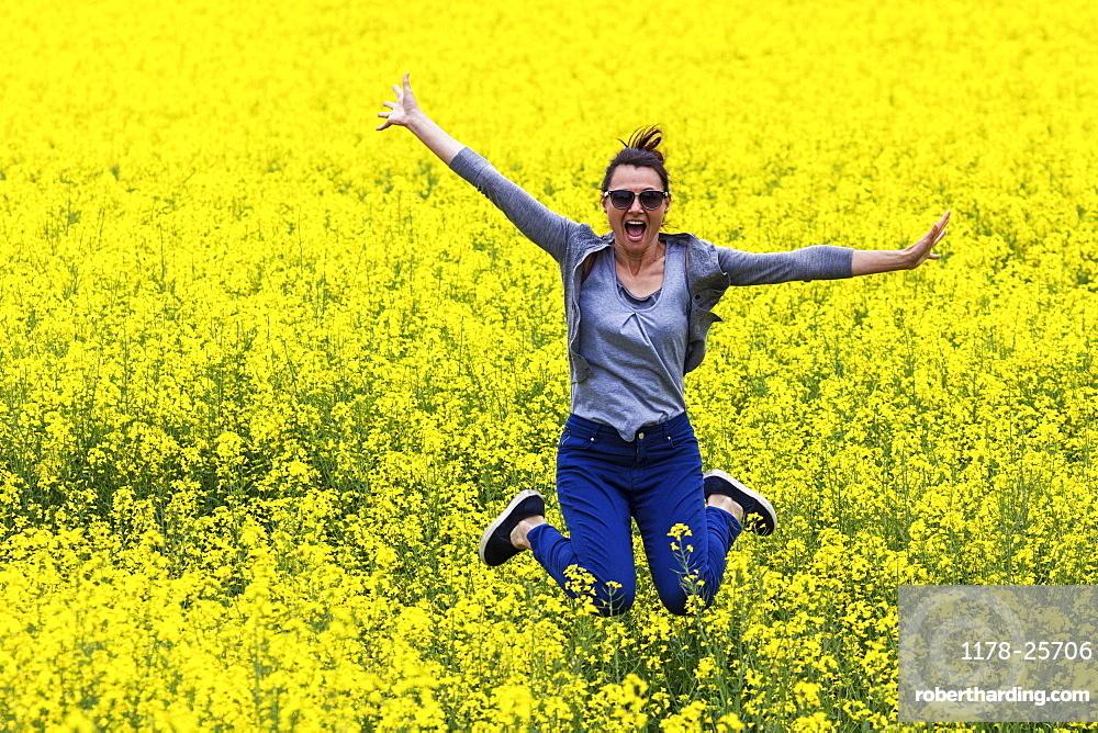 Italy, Tuscany, Woman jumping in canola field