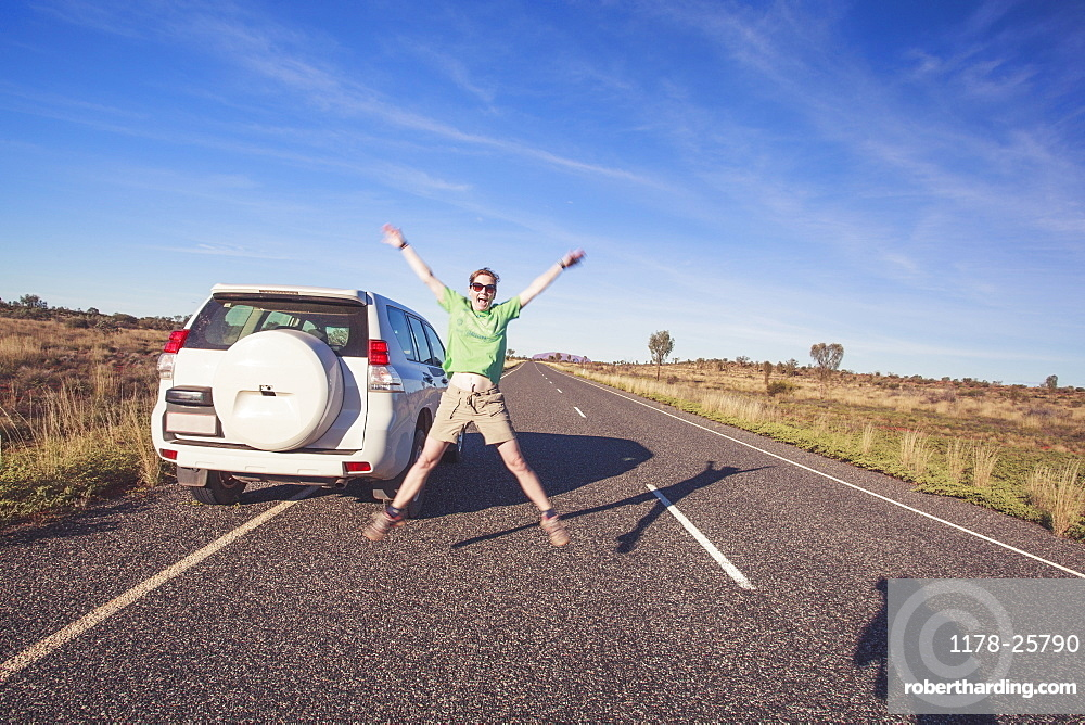 Australia, Outback, Northern Territory, Red Centre, Uluru-Kata Tjuta National Park, Woman jumping next to SUV car on road in wilderness