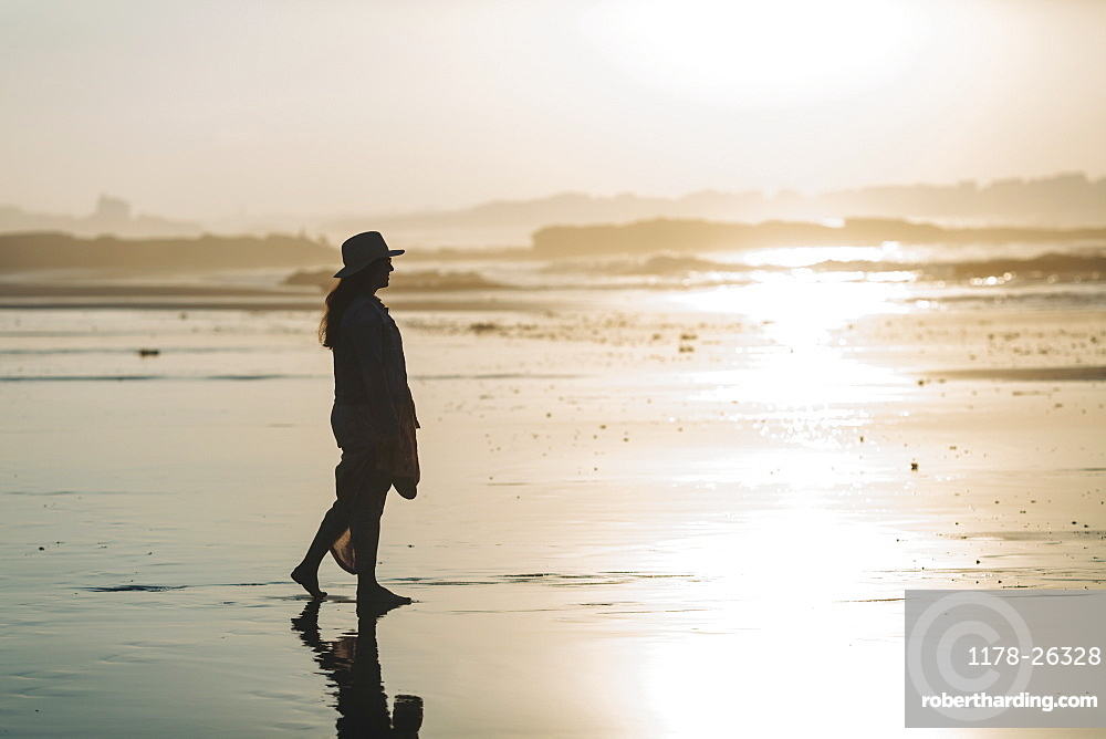 Silhouette of woman on beach at sunset