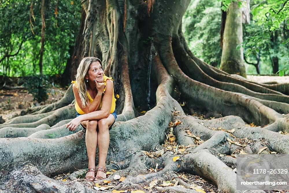 Woman sitting on roots of tree