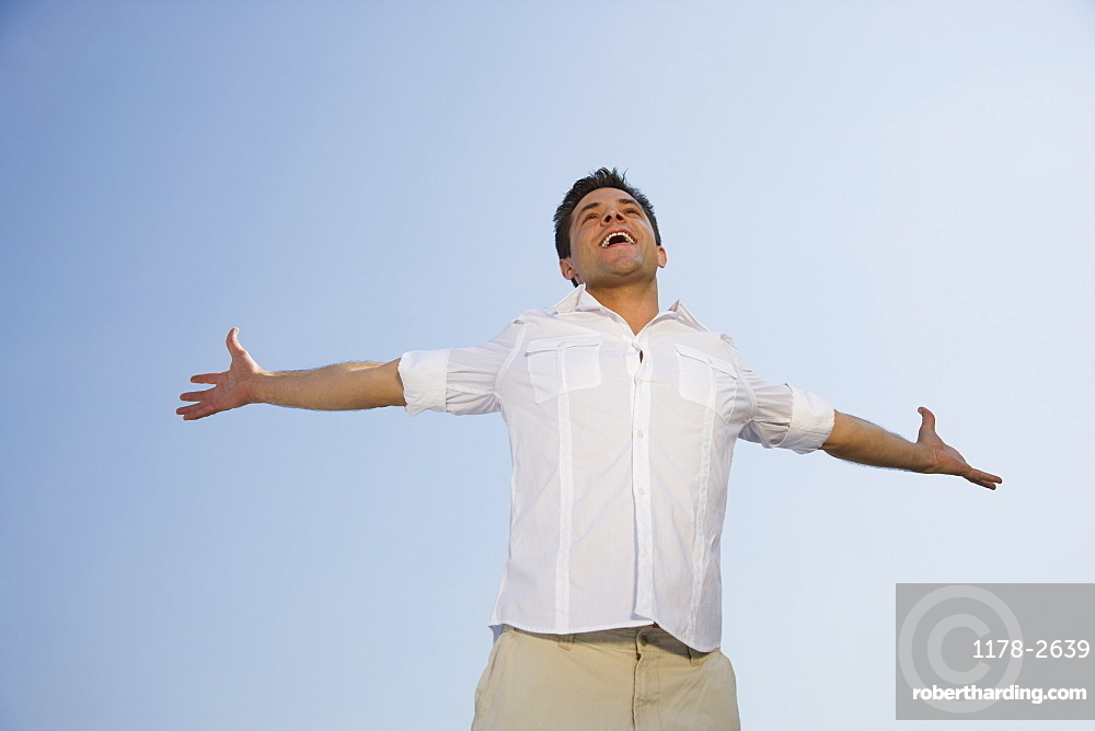Low angle view of man with arms outstretched