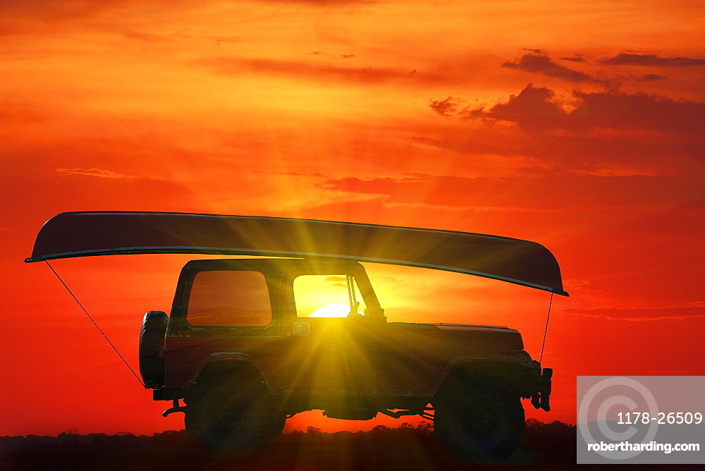 Canoe on top of Jeep at sunset