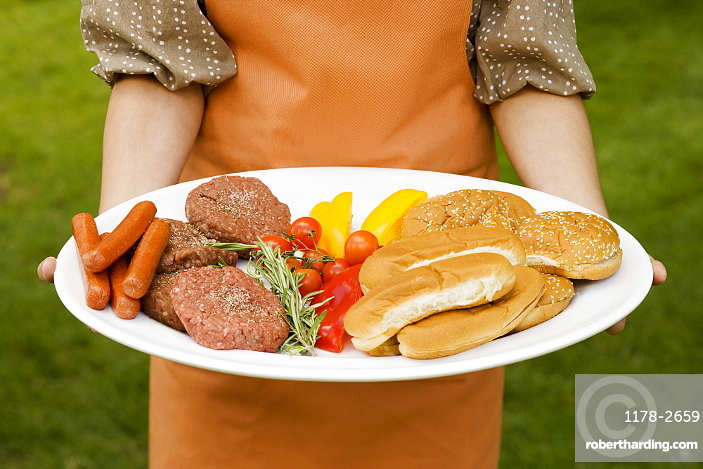 Person holding platter of food for barbeque