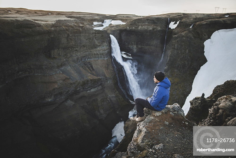 Hiker sitting on cliff by Haifoss waterfall in Iceland