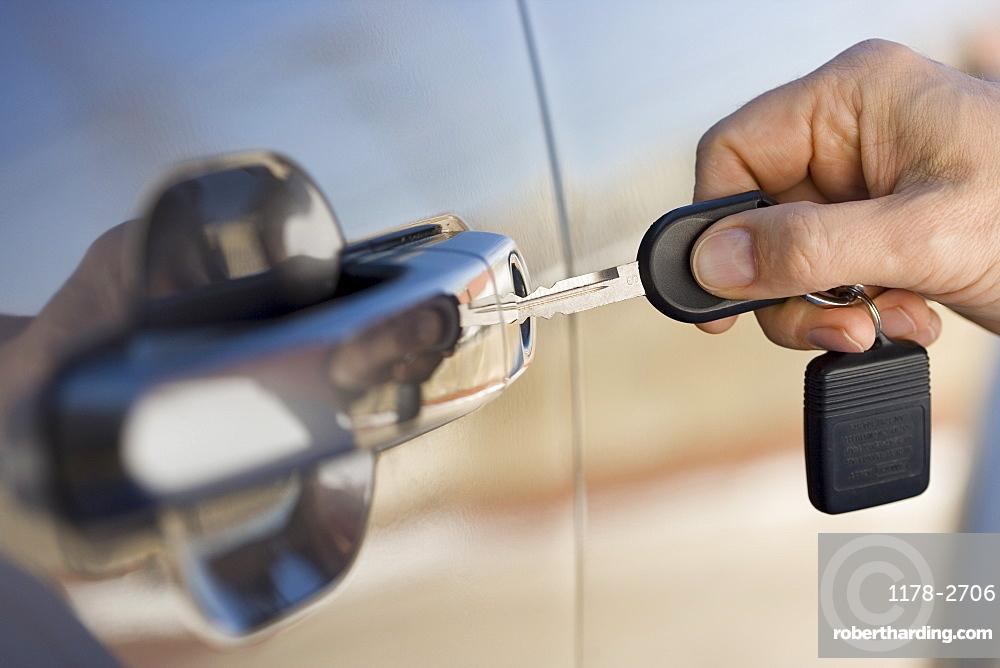 Man putting car key in door