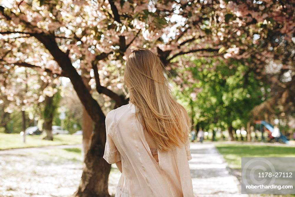 Blond haired woman by blossoming trees