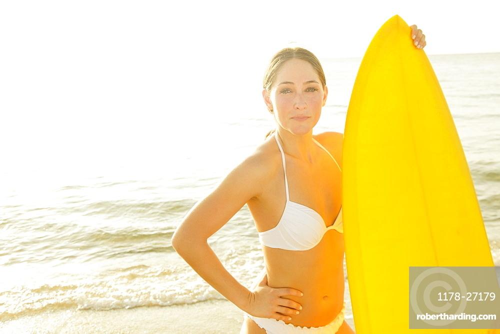 Woman wearing white bikini holding surfboard
