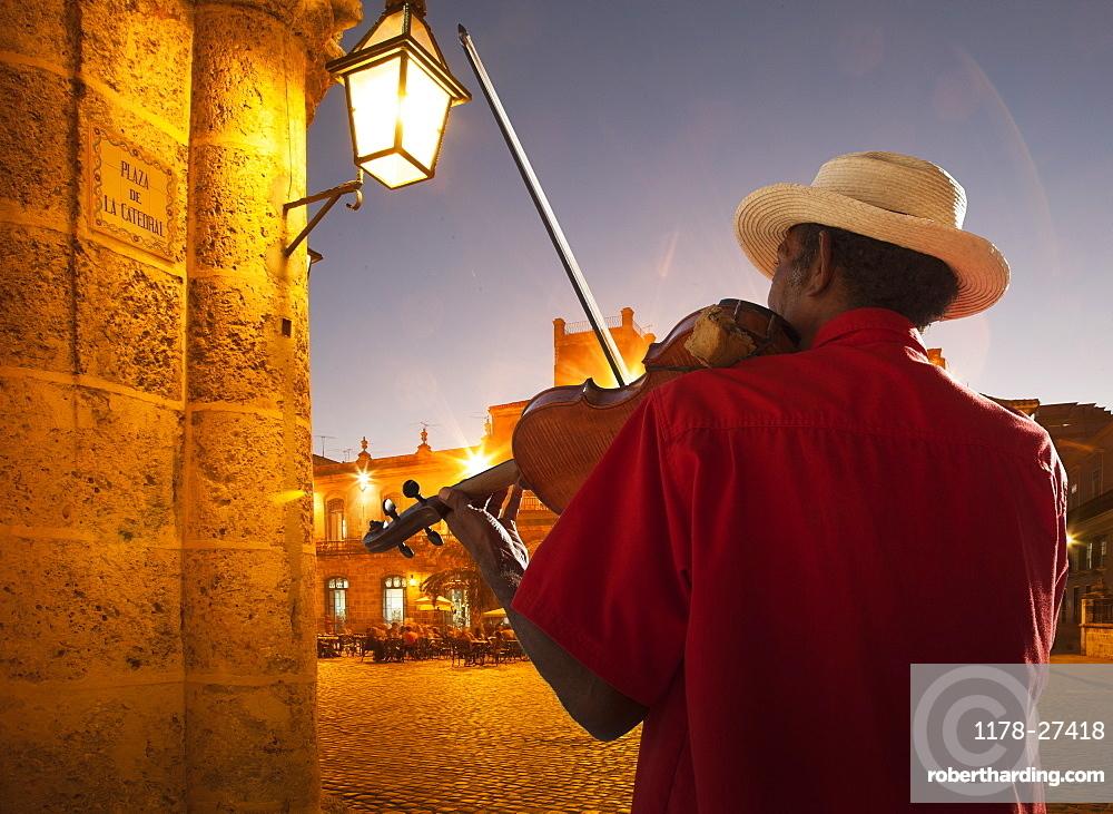 Senior man playing violin at night in Plaza de la Catedral, Havana, Cuba