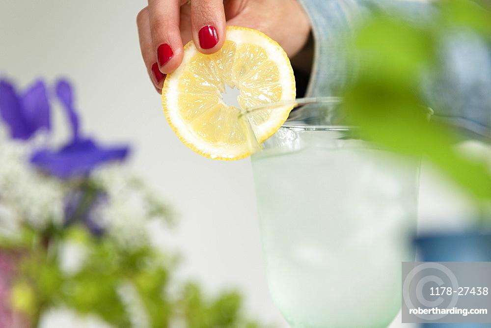 Woman putting lemon slice on glass of water