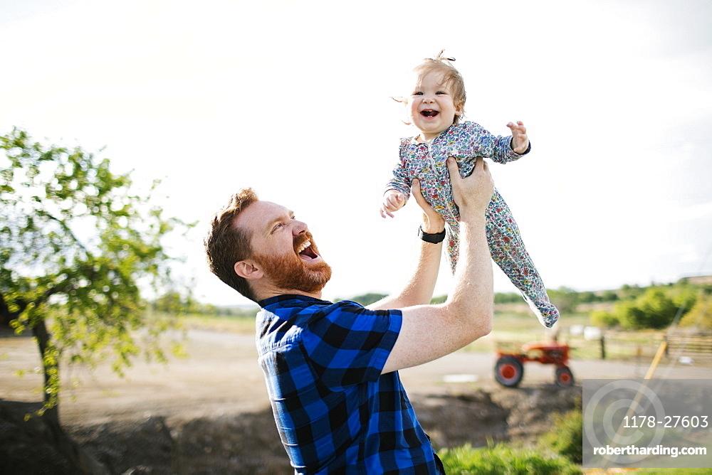Father lifting baby girl