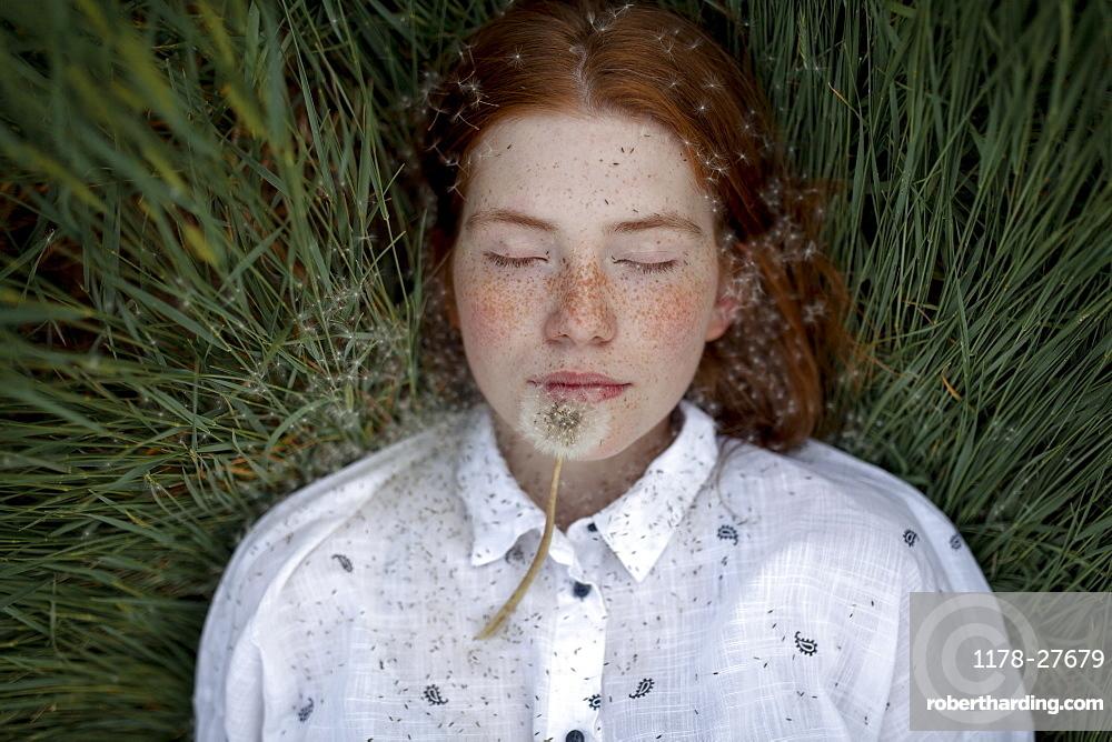 Teenage girl lying down with dandelion seedhead