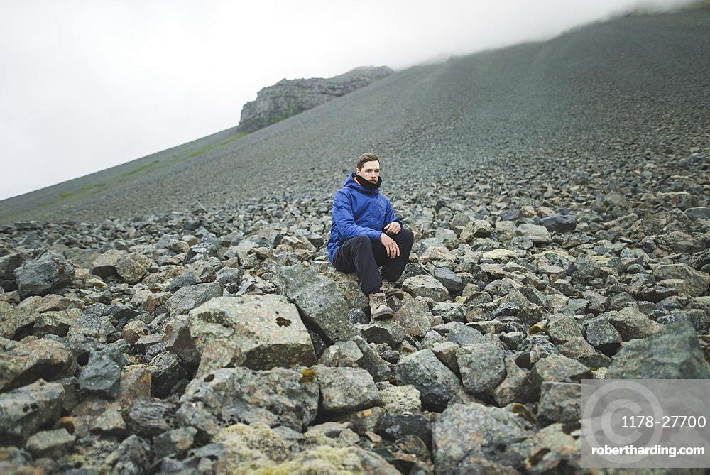 Young man sitting on rock hill in Kirkjubµjarklaustur, Iceland