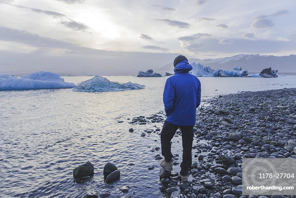 Man wearing blue coat by Jokulsarlon glacial lake in Iceland