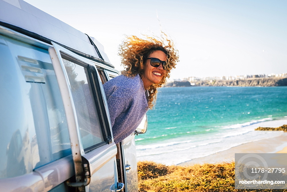 Smiling woman leaning out of camper van by beach in Fuerteventura, Canary Islands