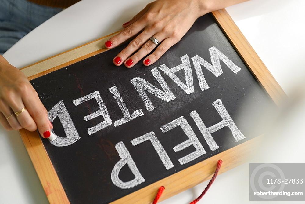 Woman writing 'Help Wanted' on chalkboard