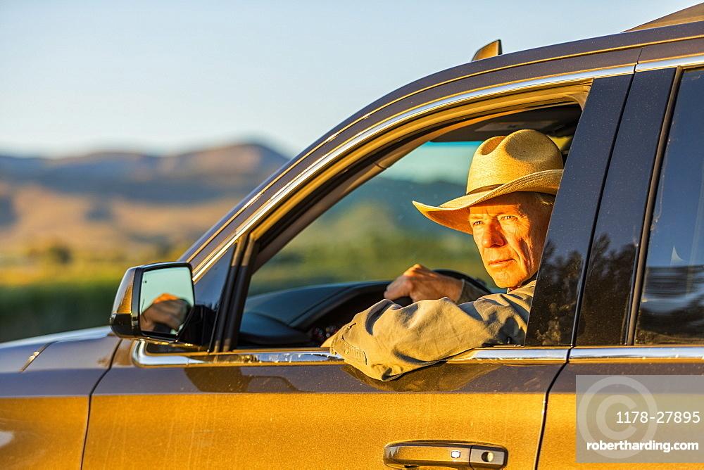 Farmer wearing cowboy hat driving SUV