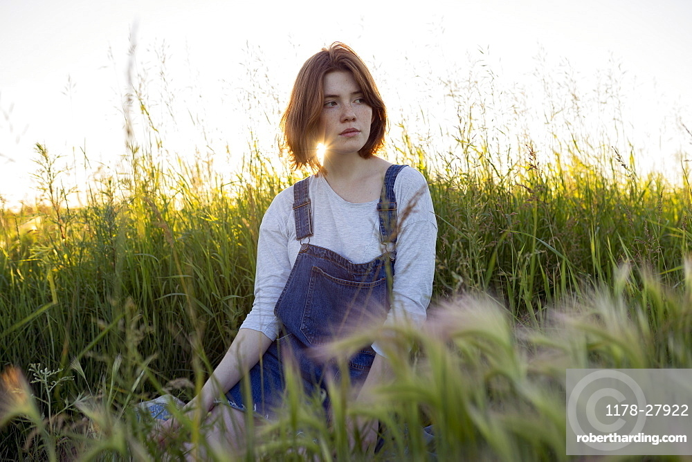 Young woman sitting in wheat field
