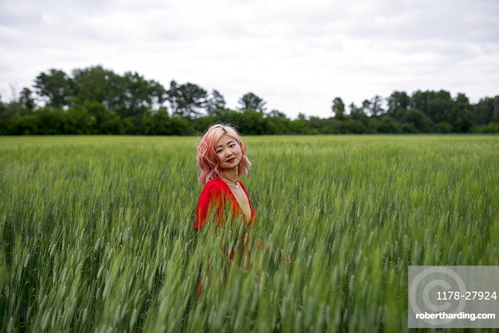 Woman with pink hair in wheat field