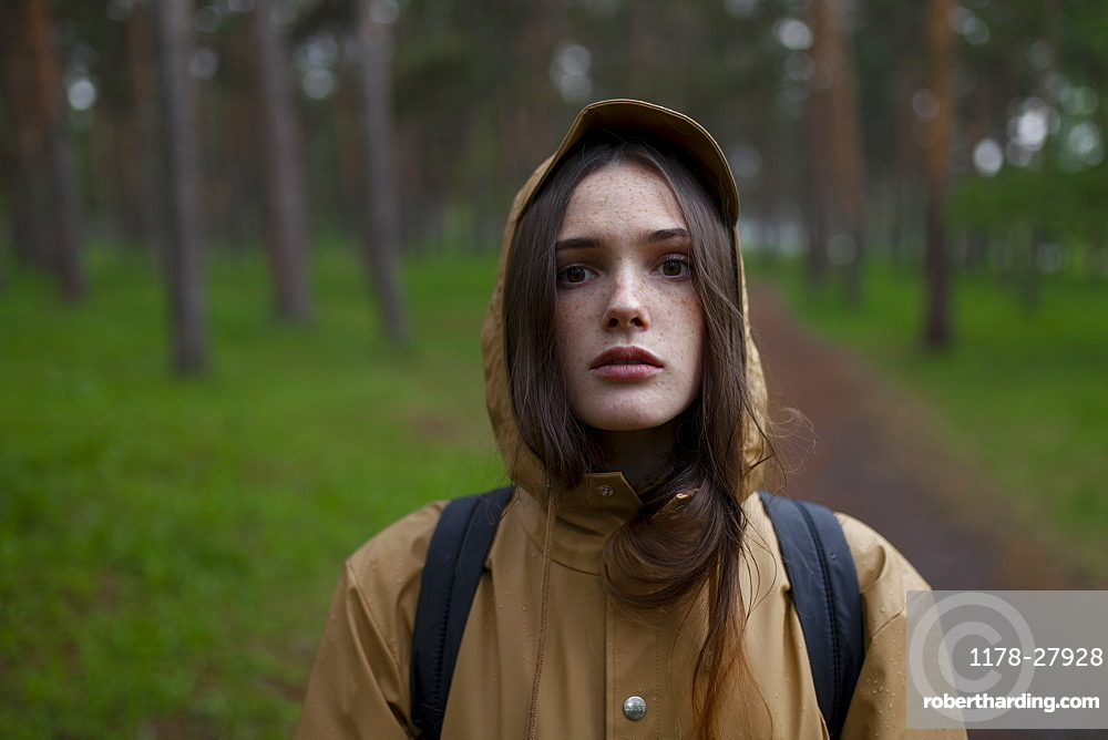 Portrait of young woman wearing brown raincoat