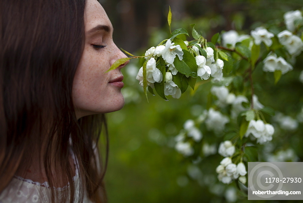 Young woman with her eyes closed sniffing flowers