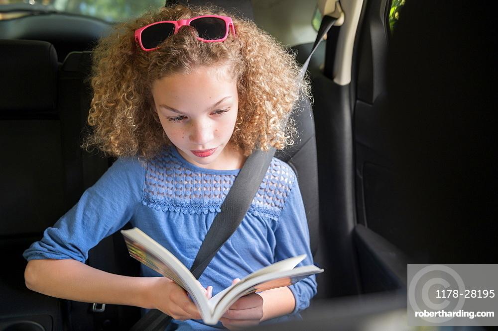 Girl reading book in car