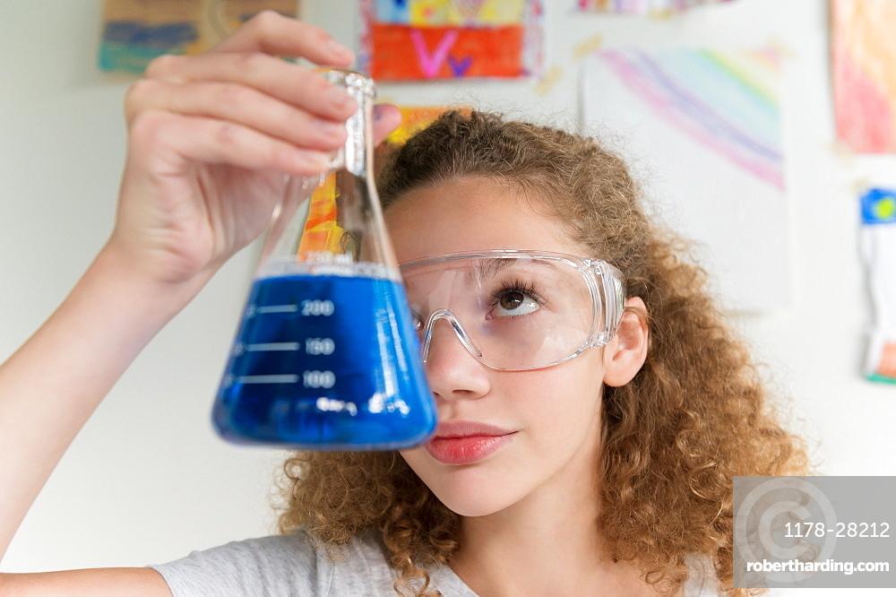 Girl holding beaker of blue liquid