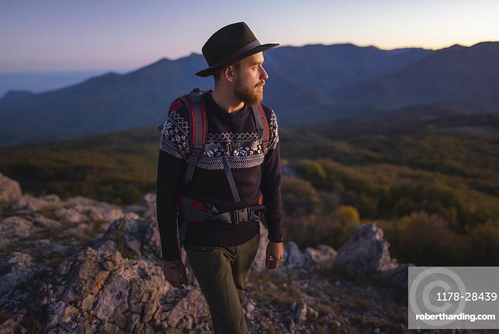 Man against mountain range at sunset