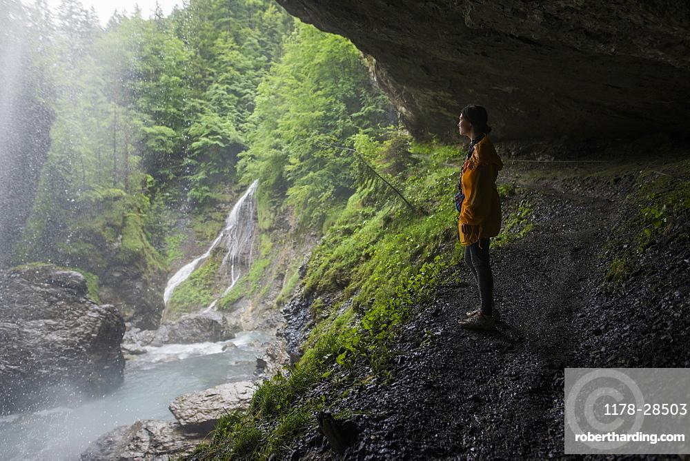 Woman in jacket by waterfall