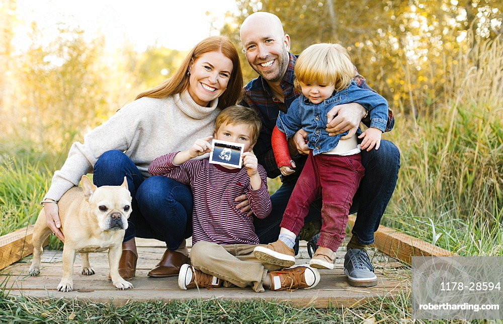 Smiling family with ultrasound photograph and pet dog on forest boardwalk