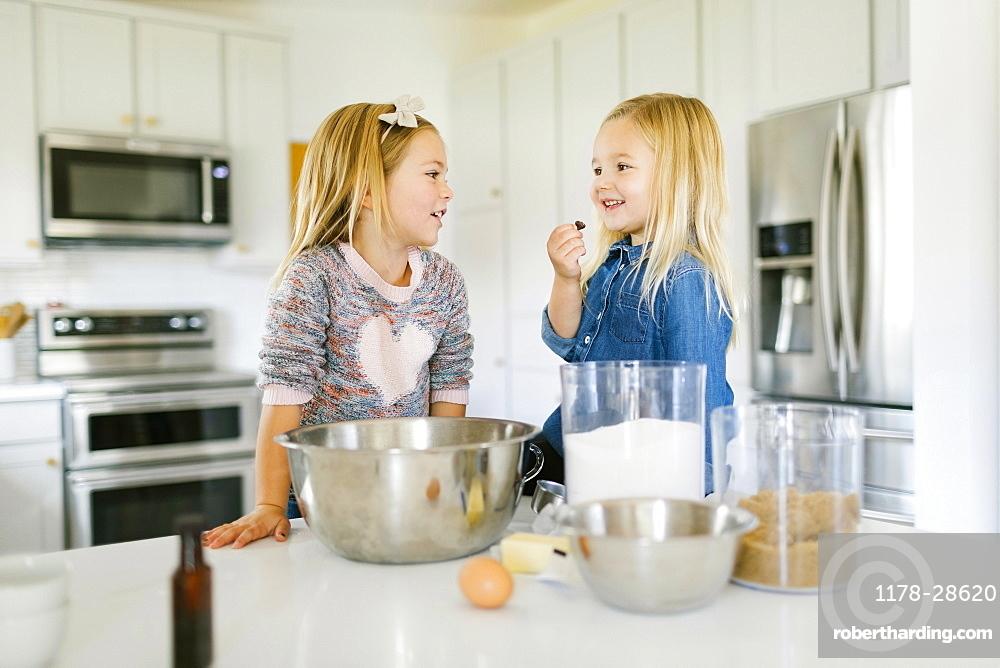 Smiling girls baking cookies