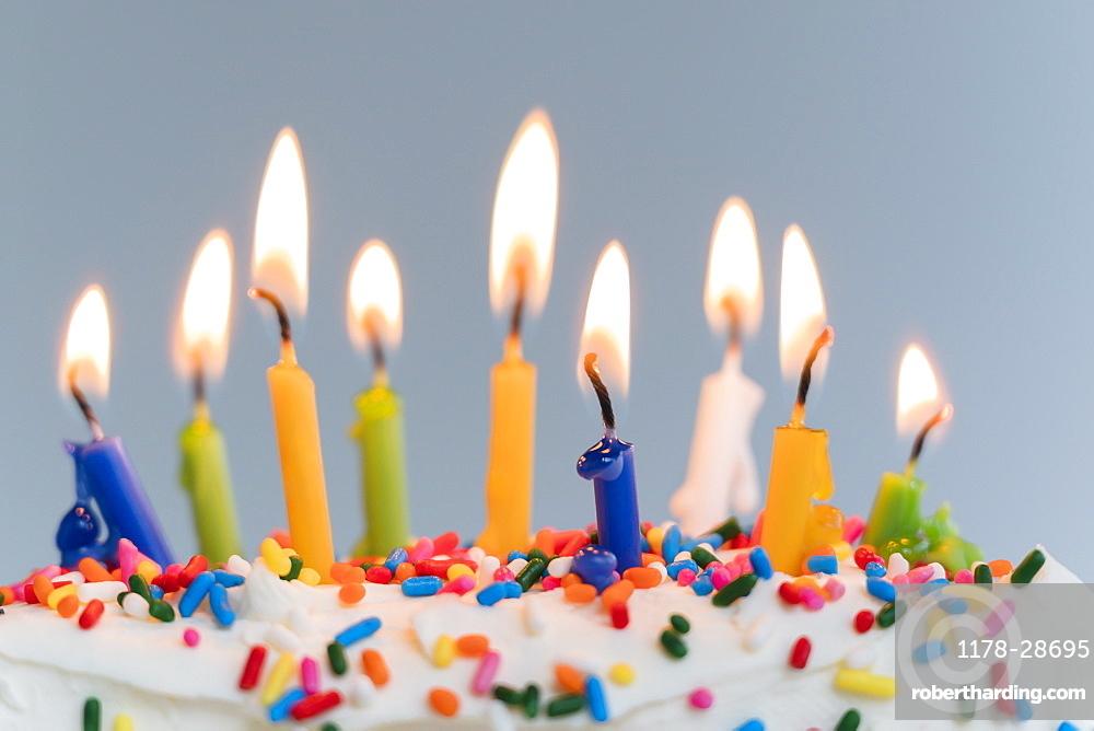 Lit birthday candles on cake